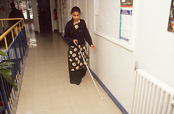 Young girl with visual impairment walking along corridor using white stick,