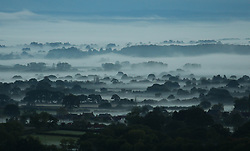 © Licensed to London News Pictures. 11/10/2014. Somerset, UK Fog in Somerset , pictured from Buckland St Mary in the Blackdown hills looking towards Central Somerset before sunrise today . Photo credit : Jason Bryant/LNP