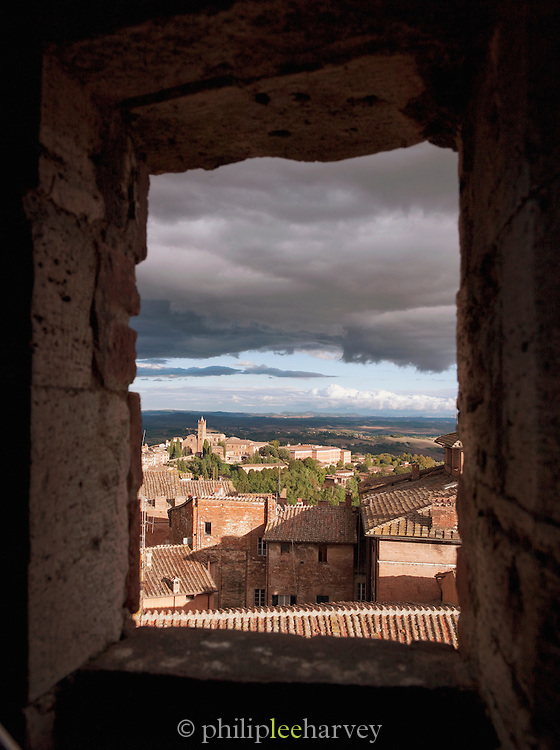 Old buildings of Siena, and the landscape of Tuscany stretching into the distance in Italy. Here seen from Facciatone, an unfinished extension of the Duomo di Siena