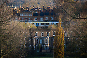 A Thameslink commuter train carriage passes suburban terraced houses and Victorian-era flats, seen from Herne Hill's Brockwell Park, on 19th November 2020, in Lambeth, London, England.
