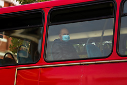 © Licensed to London News Pictures. 17/04/2020. London, UK. A passenger on a bus wearing a face mask as a precaution against the COVID-19 as coronavirus lockdown continues. The Mayor of London, Sadiq Khan has called for all passengers to wear face masks on public transport after 26 TfL workers, including 16 bus drivers, have died from COVID-19. Photo credit: Dinendra Haria/LNP