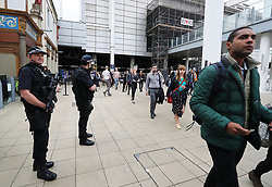 Armed police in front of scaffolding covering the entrance into the Manchester Arena from the adjacent Manchester Victoria railway station which has reopened for the first time since the terror attack in which a suicide bomber killed 22 people a week ago.