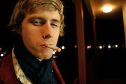 Tom Beecham, frontman of Seattle pop rock band The Raggedy Anns, smokes a cigarette at night outside a rehearsal studio in Seattle, Washington.
