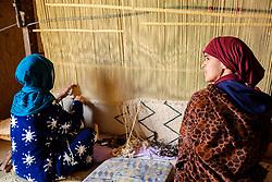 Women weaving a carpet in a  ruined, but still occupied,  kasbah near  Tazenakht, southern Morocco, Africa<br /> <br /> (c) Andrew Wilson   Edinburgh Elite media