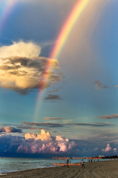 Rainbow Beach: A bold rainbow cuts the evening sky over-top of a tranquil, tropical beach scene as locals play amongst the oceans waves, Varadaro Cuba.