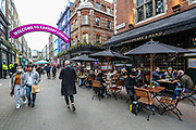 """People sit, drinking and eating, outside cafes and pubs in Soho, central London, on Tuesday, April 13, 2021. Some of England's coronavirus lockdown restrictions were eased by the British government on Monday, April 12, 2021. People across England can get their hair cut, eat and drink outside at restaurants and browse for clothes, books and other """"non-essential"""" items as shops and gyms reopened Monday after months of lockdown. (Photo/ Vudi Xhymshiti)"""