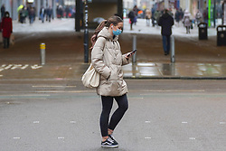 © Licensed to London News Pictures. 31/12/2020. Manchester , UK.  A woman wearing a face covering  walks in central Manchester this morning.  The county of Greater Manchester from Thursday 31 December will move into Tier 4 following a spike in coronavirus cases. Photo credit: Ioannis Alexopoulos/LNP