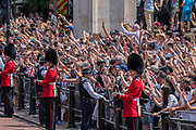 """The crowds greet Kate and Harry as they return down the Mall - Trooping the Colour by the Irish Guards on the Queen's Birthday Parade. The Queen's Colour is """"Trooped"""" in front of Her Majesty The Queen and all the Royal Colonels.  His Royal Highness The Duke of Cambridge takes the Colonel's Review for the first time on Horse Guards Parade riding his horse Wellesley. The Irish Guards are led out by their famous wolfhound mascot Domhnall and more than one thousand Household Division soldiers perform their ceremonial duty. The Soldiers will parade in the traditional ceremonial uniforms of the Household Cavalry, Royal Horse Artillery, and Foot Guards. They are accompanied by the Household Division Bands & Corps of Drums. London 17th June 2017."""