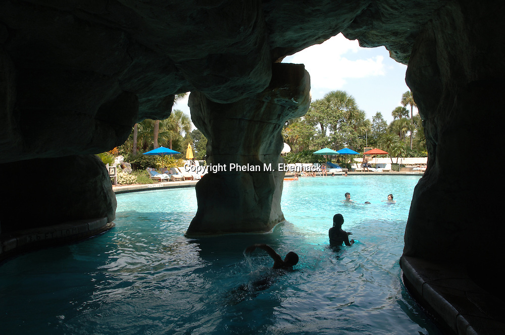 Swimmers make their way through a man-made cave in the massive pool outside the Hyatt Grand Cypress Resort in Orlando, Florida.