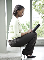 June 17, 2010 - A black businesswoman working on a notebook computer while sitting on a window ledge in a convention center lobby. (Credit Image: © Mint Images via ZUMA Wire)