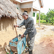 CAPTION: Christpoher Onyimo farms a variety of different fruits and cereals, including oranges, mangoes, pineapples, green grams and groundnuts. Here, we see him using a machine to remove groundnuts from their shells. LOCATION: Apapai Parish, Otuboi Sub-county, Kalaki County, Kaberamaido District, Uganda. INDIVIDUAL(S) PHOTOGRAPHED: Christopher Onyimo.