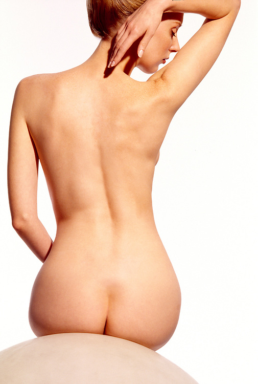 Rear view of shapely nude woman sitting on globe with hand caressing face in profile