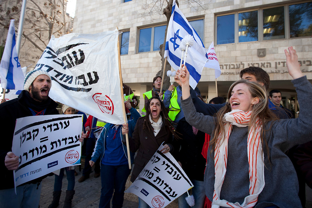 Protesters hold banners and chant slogans during a demonstration against the current employment status of contract workers, at the entrance to the National Labor Court in Jerusalem, Israel, on January 9, 2012, prior to a hearing on the petition of the Histadrut Labor Federation to allow it to hold a general strike on behalf of contract workers over their employment status.