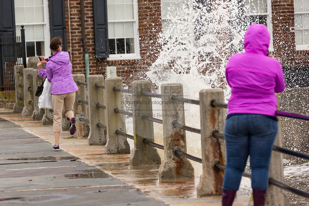 Tourists jump back from ocean spray as high tides and flooding continued to plague the historic district after record breaking storms dumped more than two feet of rain on the lowcountry October 5, 2015 in Charleston, South Carolina.