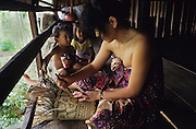 1991: Kenyah natives, women and children. She is weaving a traditional rattan sack from rainforest materials, on longhouse verandah. Long Geng, Belaga district, Sarawak, Borneo<br /> <br /> Tropical rainforest and one of the world's richest, oldest eco-systems, flora and fauna, under threat from development, logging and deforestation. Home to indigenous Dayak native tribal peoples, farming by slash and burn cultivation, fishing and hunting wild boar. Home to the Penan, traditional nomadic hunter-gatherers, of whom only one thousand survive, eating roots, and hunting wild animals with blowpipes. Animists, Christians, they still practice traditional medicine from herbs and plants. Native people have mounted protests and blockades against logging concessions, many have been arrested and imprisoned.