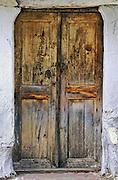 Old wood door with faded yellow paint, in Kastraki, Meteora, Greece.