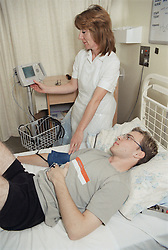 Young man suffering from Crohn's Disease lying in bed on spinal unit of hospital while patient assistant checks his blood pressure,