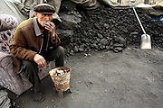 A coal yard worker in Korla smakoes as he waits for customers, April 12, 2006. Mass quantities of air pollutants from China, including mercury discharged from traditional coal-fired power plants, are travelling to places as far away as the US, according to the US environment agency.