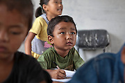 Young boy looks up at teacher in his nursery class room learning to write at the GoodWeave centre in Attarkhen, Kathmandu, Nepal.  They are children of carpet factory workers, and have been supported into education by GoodWeave, a charity that works towards getting children out of factories and into education.  Previously these children would have been left unattended in the factory while their parents worked as their low salary could not cover childcare costs. GoodWeave were recipients of the Stars Foundation's Impact Award.
