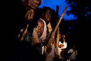 """A child joins a group of 'arrow boys"""" holding a hoe as a weapon. The arrow boys are a self defense group created to stop LRA attacks."""