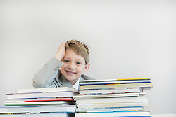 Portrait of boy with stack books, smiling