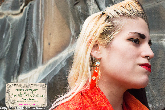 """Flower feather photo jewelry earrings by Star Nigro<br /> <br /> Materials: orange flower photo, 22K gold accents, orange feathers, swarovski crystals, sterling silver earring hooks<br /> <br /> size: 2"""" x 1/8""""<br /> <br /> price: $64.00<br /> <br /> photo jewelry: Star Nigro<br /> <br /> model:Palma Latorre artist/fx artist<br /> gorgeousfrankenfx.wixsite.com/gffx<br /> https://www.facebook.com/GF.effects/<br /> <br /> photo by Star Nigro<br /> <br /> StarNigro.com<br /> <br /> ©2021 All artwork is the property of STAR NIGRO.  Reproduction is strictly prohibited."""
