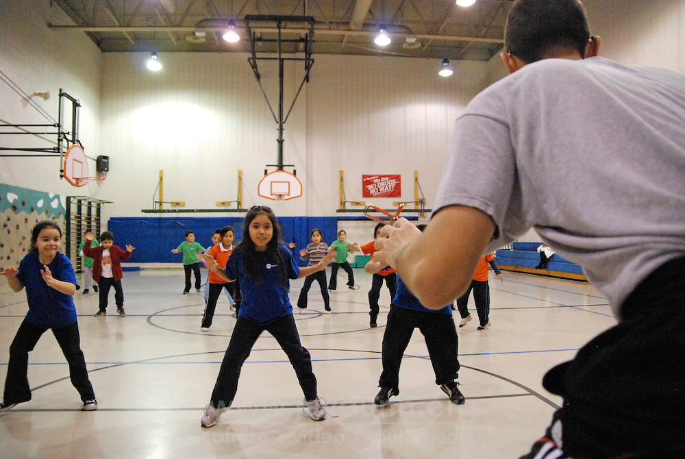 """USA, Chicago, IL, December 16, 2009.  Volunteer Michael Torres leads """"foot fire,"""" a strength drill. Founded ten years ago by Rob and Amy Castaneda, """"Beyond the Ball"""" is a non-profit organization dedicated to giving kids and parents a healthy place to play together, whether it be in an after-school program or during an summer series of playground days, like last year's wildly successful """"Project Play."""" The predominantly working-class neighborhoods of Little Village and North Lawndale have no park, and little public space for families that is safe from the gang violence endemic to large US cities. Beyond the Ball's approach is personal, and takes a long-term view - both Rob and Amy are neighborhood residents, and have experienced first-hand the anger of gang members. The group arranges for school facilities to be open late, such as this gym at Josefa Ortiz de Dominguez Elementary, and welcomes student volunteers who also get credit from Chicago Public Schools for doing community service. Many of the teenagers working with """"Beyond the Ball"""" are comfortable as mentors, because they've been in the program before. It is easy to see the pride they take in teaching and taking responsibility for the younger kids, and how such a positive approach to neighborhood building can work. Photo for Hoy by Jay Dunn."""