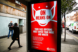 © Licensed to London News Pictures. 16/10/2020. London, UK. A woman wearing a face covering walks past the Transport for London's COVID-19 advert as London moves to COVID-19 tier two restrictions from tonight, following the government's announcement of tougher measures in the capital to manage increasing cases. From midnight tonight, households in London will not be allowed to mix indoors, including in pubs and restaurants.  Photo credit: Dinendra Haria/LNP
