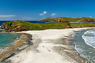 """A thin isthmus """"separates the Caribbean Sea from the Atlantic Ocean"""" on the far west end of St. Thomas, US Virgin Islands. This view is from land above the isthmus."""