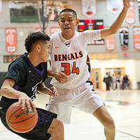 Gallup Bengals power forward Brad Lynch (34) defends  Miyamura Patriots small forward Darin Baca (24) near the baseline during the 4A -District Tournament Championship game at Gallup High School Saturday.