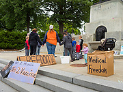 """18 MAY 2020 - DES MOINES, IOWA: People in a prayer circle during an anti-vaccine prayer vigil. About eight adults, and their children, gathered in the front of the Iowa State Capitol in Des Moines Monday for a prayer vigil against mandatory vaccines. Iowa state law allows the governor to mandate vaccines for communicable diseases during a public health emergency and the """"anti-vaxxers"""" are afraid the government will mandate a vaccine for Coronavirus (SAR-CoV-2) if one is developed. As of May 18, 355 people in Iowa have died from COVID-19, the disease caused by the Coronavirus (SARS-CoV-2), and 14,955 have tested positive for the Coronavirus.               PHOTO BY JACK KURTZ"""