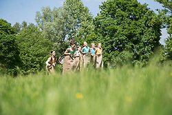 Group of girls playing in sack race on a field, Munich, Bavaria, Germany