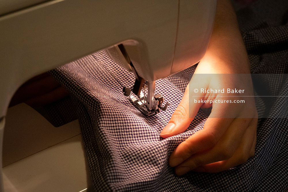 Using her own sewing machine, a young dressmaking hobbyist woman sews together the seams of a home-made dress that she's created from a pattern in her home, on 6th March 2021, in London, England.