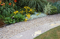 Border and lawn separated by gravel path and tiled mosaic