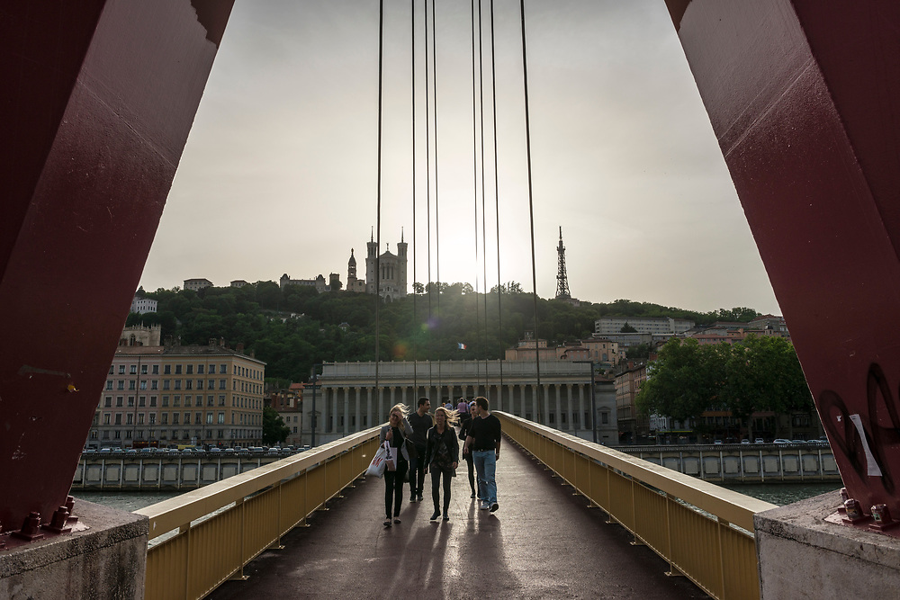A group of young adults cross a pedestrian bridge in Lyon, France
