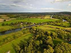 The afternoon sun illuminates the lush English landscape and the River Thames towards Marlow, Bucks, at Aston near Henley-On-Thames, Oxfordshire as the colours of autumn behind to appear on the trees. Henley On Thames, October 01 2018.