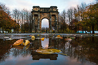 McLennan Arch reflected alongside leaves in a puddle at Joycelyn Gate, Glasgow Green