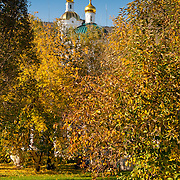 Купола Никольской церкви над желтыми деревьямив Оренбурге