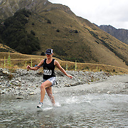Runner Mel Wenlock crosses Moke Creek on the Ben Lomond High Country Station during the Pure South Shotover Moonlight Mountain Marathon and trail runs. Moke Lake, Queenstown, New Zealand. 4th February 2012. Photo Tim Clayton