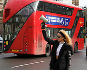 A woman holding a megaphone uses sound effects to cause disruption outside Parliament in London in an attempt to stop the new protest restriction laws.