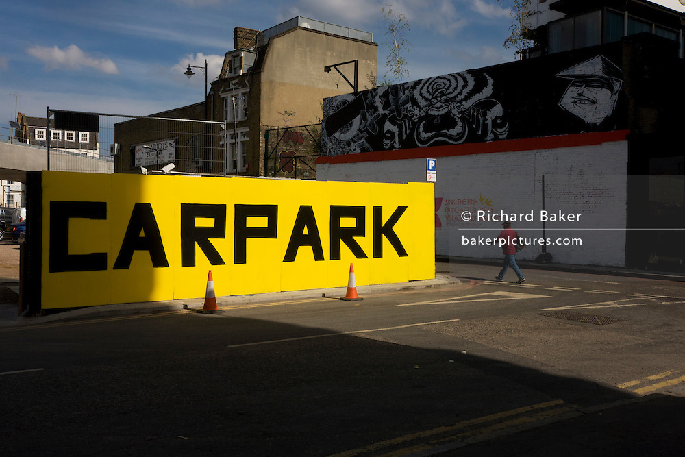 Man walks past a large yellow car park sign on street in East London.