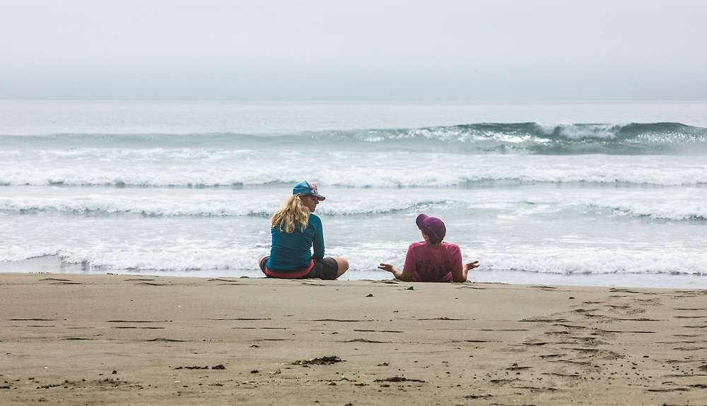 Two women relaxing and talking on the beach, 2nd Beach, Olympic National Park and Olympic Coast National Marine Sanctuary.