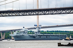 North Queensferry, Scotland, UK. 23 May 2019. Aircraft carrier HMS Queen Elizabeth sails from Rosyth in the River Forth after a visit to her home port for a refit. She returns to sea for Westlant 19 deployment and designed to focus on the operations of her F-35 fighter aircraft. Pictured; Carrier passes underneath Queensferry Crossing and Forth Road Bridge Bridge at low tide.
