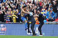 Lyle Taylor of AFC Wimbledon leaps onto Neal Ardley, the AFC Wimbledon manager as he celebrates after scoring his sides 1st goal to make it 1-0. .Skybet football league two play off final match, AFC Wimbledon v Plymouth Argyle at Wembley Stadium in London on Monday 30th May 2016.<br /> pic by John Patrick Fletcher, Andrew Orchard sports photography.