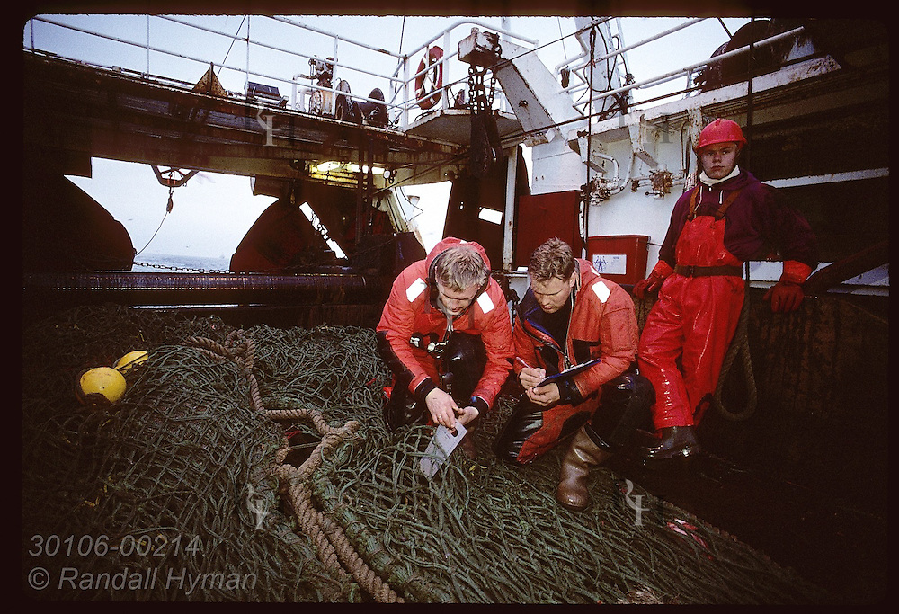Fisherman watches as men from coast guard measure net aboard trawler 60 miles off West Fjords Iceland