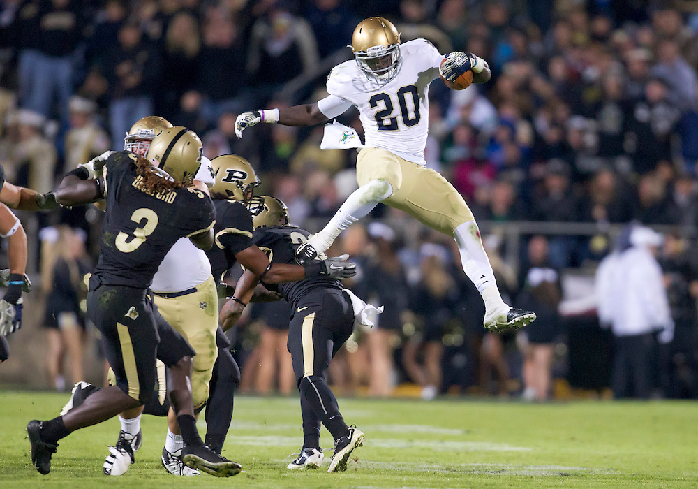 October 01, 2011:  Notre Dame running back Cierre Wood (#20) jumps over Purdue cornerback Ricardo Allen (#21) in fourth quarter action during NCAA Football game between the Notre Dame Fighting Irish and the Purdue Boilermakers at Ross-Ade Stadium in West Lafayette, Indiana.  Notre Dame defeated Purdue 38-10.