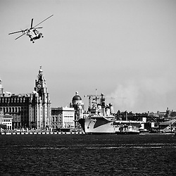 Ark Royal being towed out by the Mersey tugs before heading down the.Mersey and out to see.  She launched two helicopters to go up and down.the river.  It was a hugely popular event with crowds stretching from.Woodside to New Brighton.
