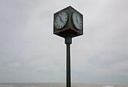Two faces of a public seafront clock cube with a background of sea, on 29th April 2017, at St Leonards, East Sussex, England.