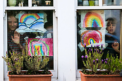 © Licensed to London News Pictures. 23/04/2020. London, UK. Children look out of the window next to their hand painted picture of colourful rainbow displayed in a house in north London. Rainbows are used as a symbol of peace and hope. Photo credit: Dinendra Haria/LNP
