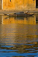 Hoi An's picturesque waterfront with a small boat in late afternoon light is seemingly mirrored in the Thu Bon river.